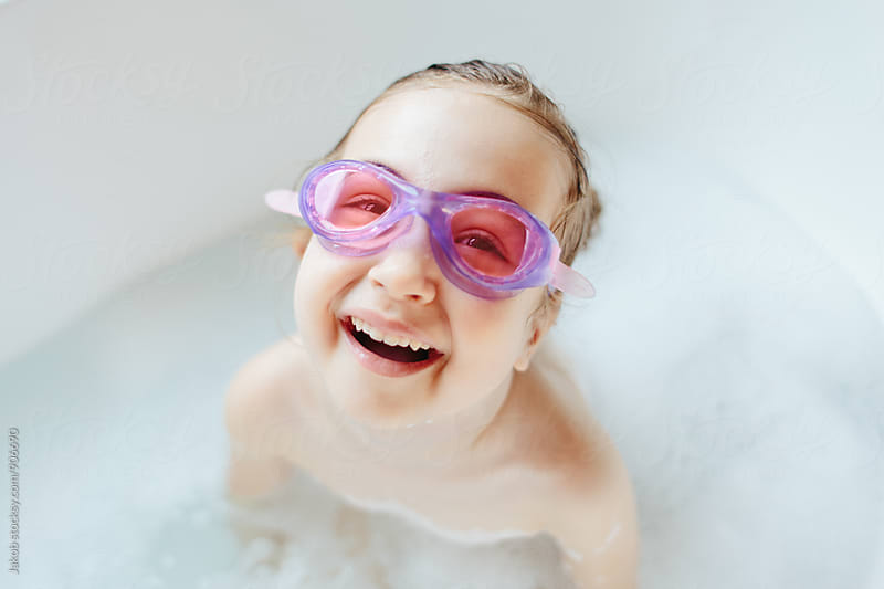 Cute young girl with swim goggles laughing in a bathtub by Jakob for Stocksy United