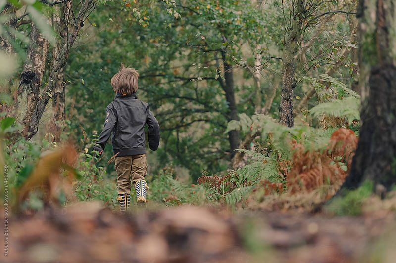 Child running through the woods by Rebecca Spencer for Stocksy United