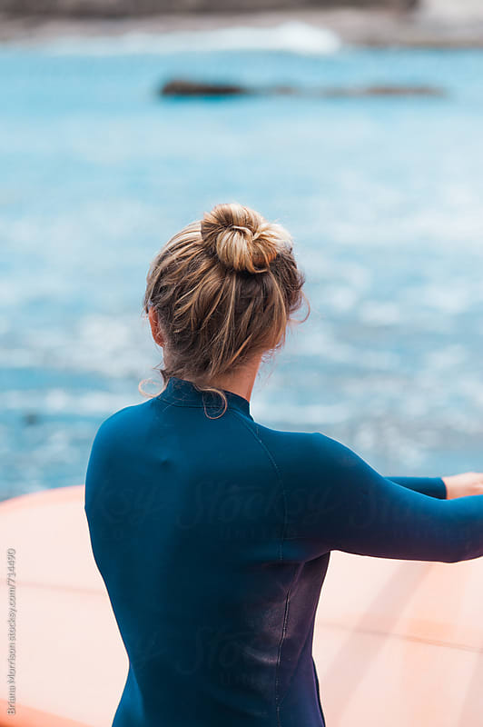 Female Surfer with Her Hair in a Bun Viewed From Behind While Looking at the Ocean by Briana Morrison for Stocksy United