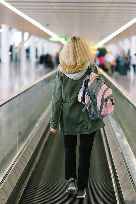 Woman Walking on Motorized Walkway in International Airport by Jeff Wasserman for Stocksy United