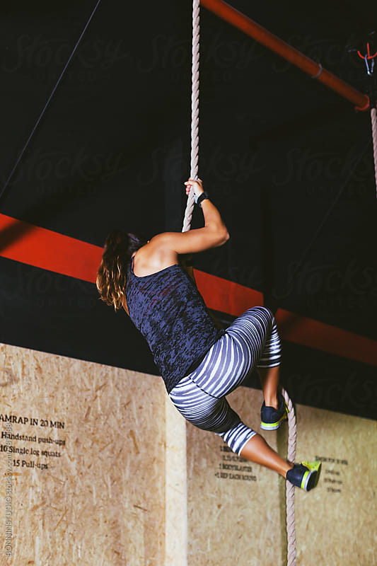 Back view of a woman climbing a rope in a gym. by BONNINSTUDIO for Stocksy United