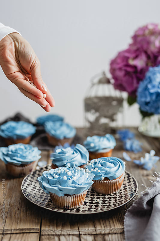 Decorating blue cupcakes by Tatjana Zlatkovic for Stocksy United