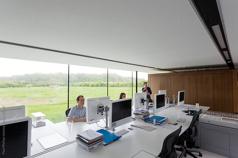 Modern office with employees behind monitors at a large table by Paul Phillips for Stocksy United