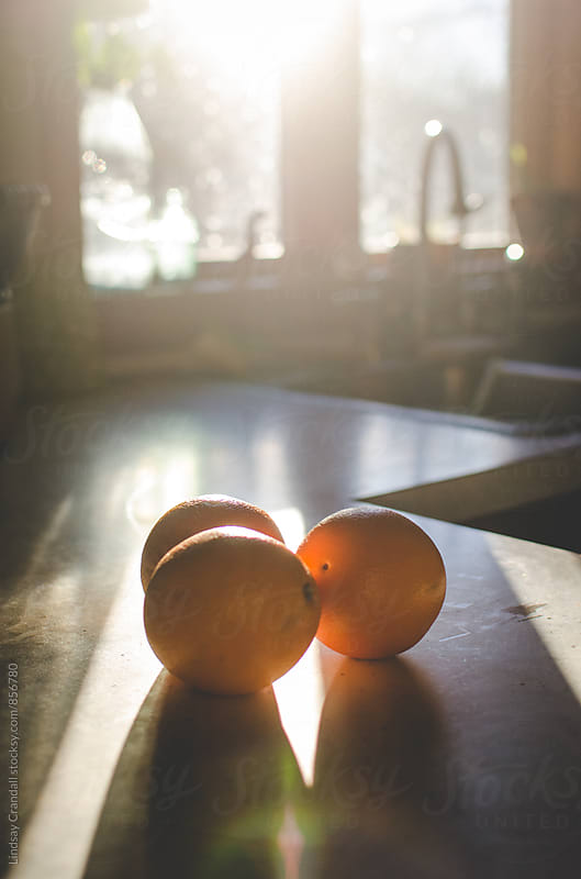 Three tasty oranges on sunlit countertop by Lindsay Crandall for Stocksy United