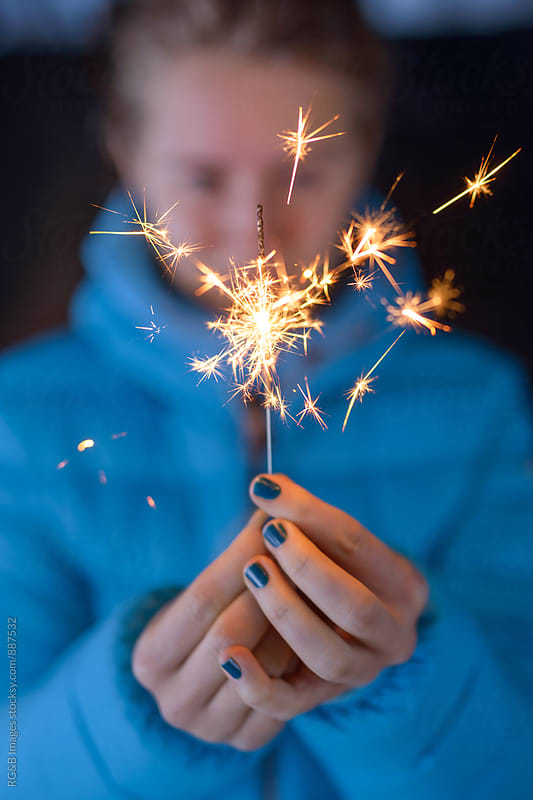 Woman holding a firework sparkler by RG&B Images for Stocksy United