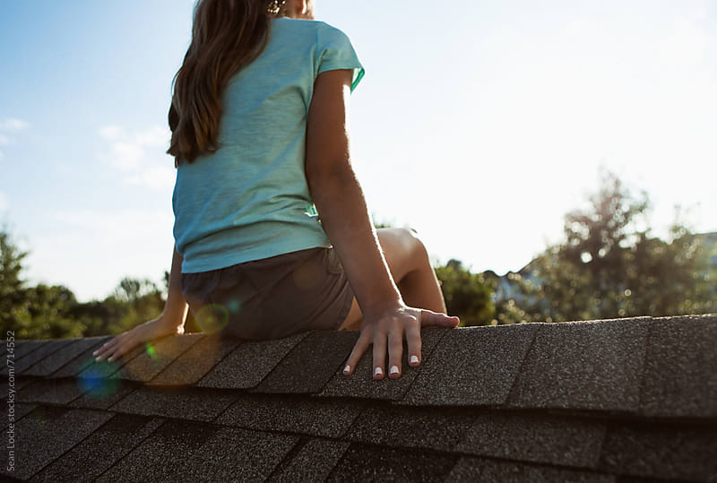 Roof: Teen Girl Sits On The Rooftop Of A House by Sean Locke for Stocksy United