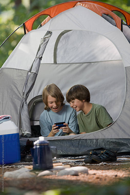 Two boys (10-11) playing computer game in tent by Andersen Ross Photography for Stocksy United