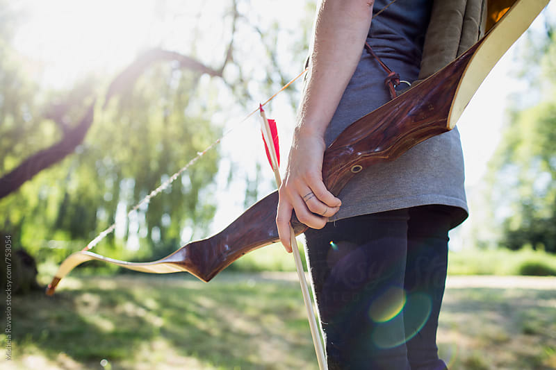 Archer standing with bow and arrow in hand by michela ravasio for Stocksy United