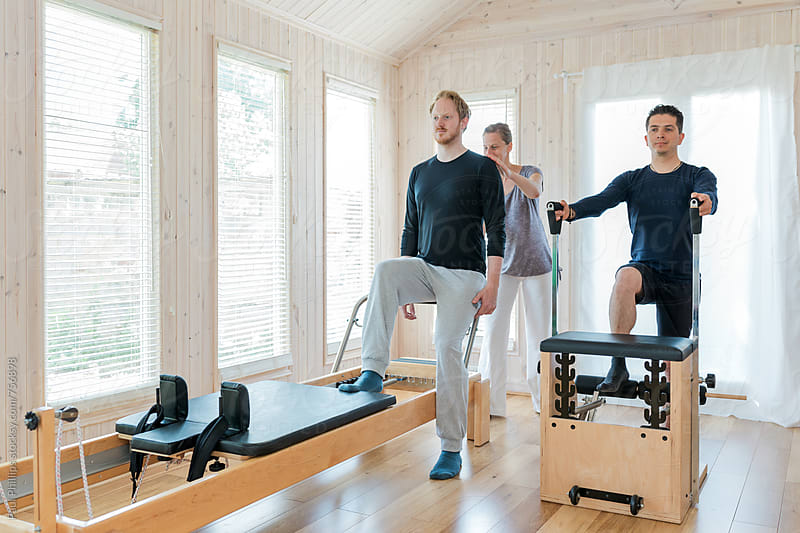 Pilates instruction with female trainer and two males. Bright modern studio. by Paul Phillips for Stocksy United