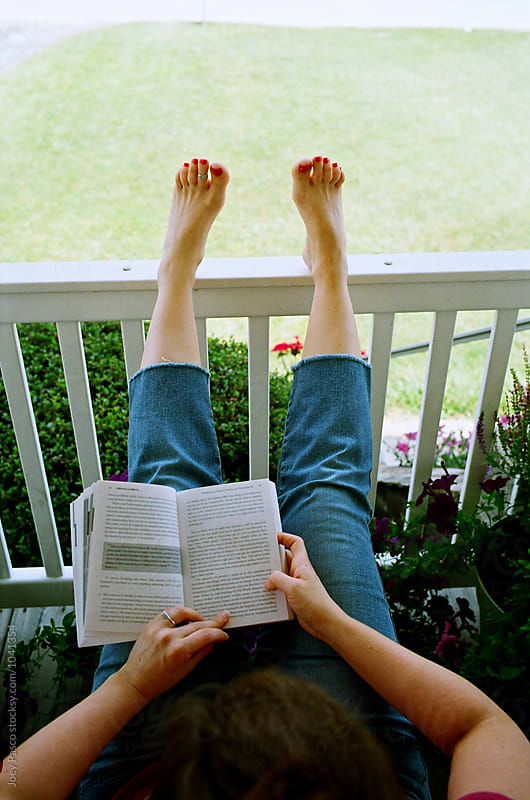 Young woman reads a book on a porch on a lazy summer afternoon by Joey Pasco for Stocksy United