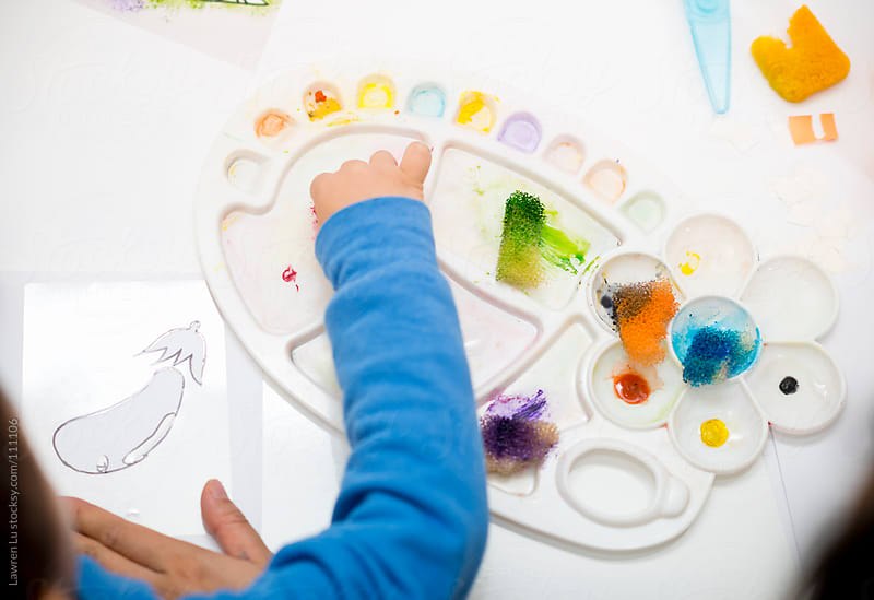 Child learning to paint by Lawren Lu for Stocksy United