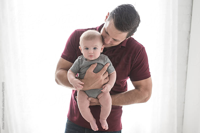 A Baby Boy Being Held By His Father by Alison Winterroth for Stocksy United