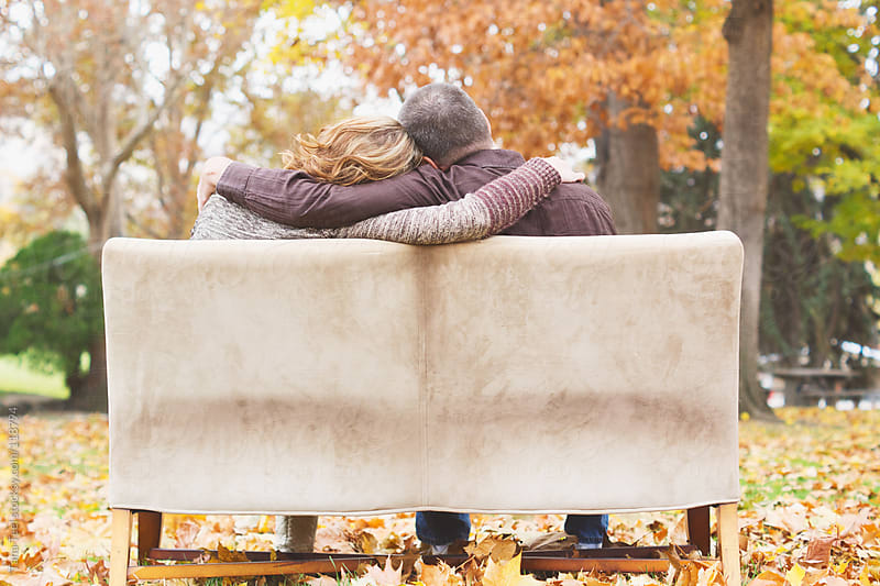 A couple hug each other while sitting on a couch in the park by Tana Teel for Stocksy United
