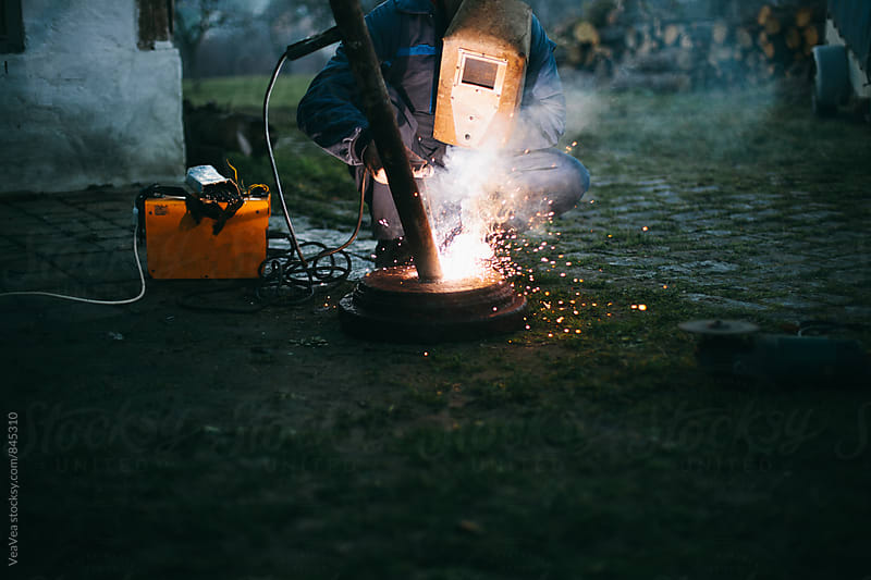 Welder welding in the backyard during sunset by VeaVea for Stocksy United