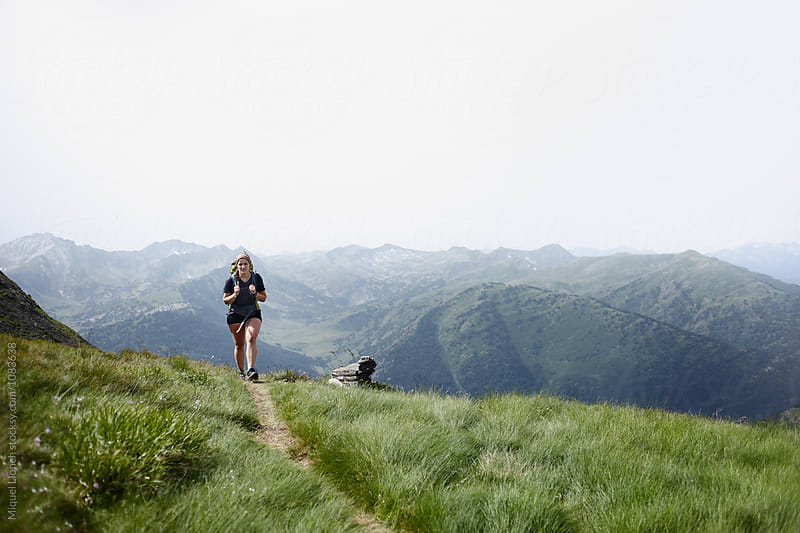 Young woman backpacking in a trail of the Pyrenees by Miquel Llonch for Stocksy United