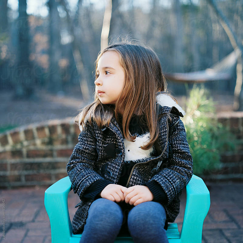 A cute young girl sitting in a chair outside by Jakob for Stocksy United