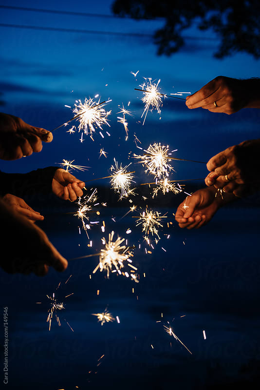 Hands holding sparklers on a summer night by Cara Dolan for Stocksy United
