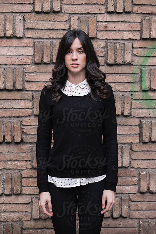 Portrait of beautiful young woman standing in front brick wall. by BONNINSTUDIO for Stocksy United
