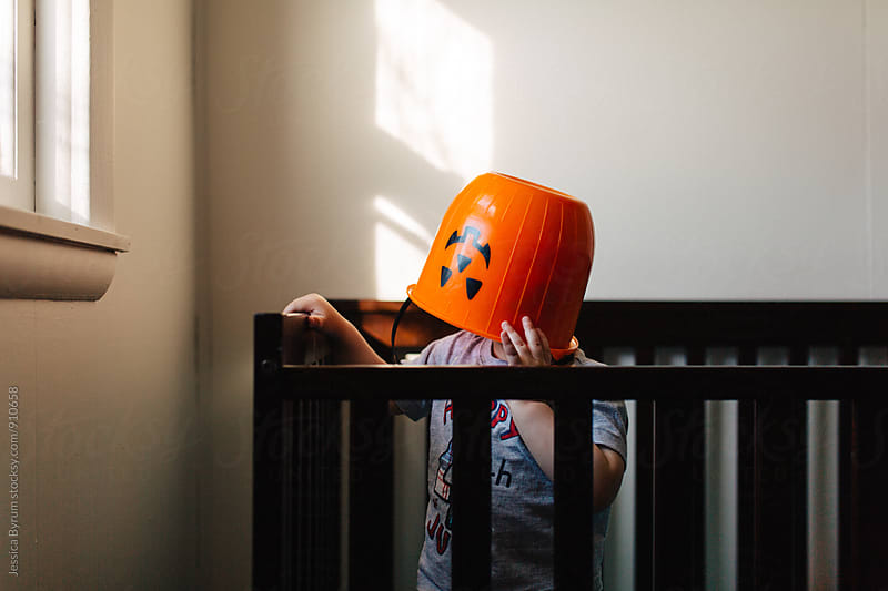 Little boy with halloween bucket on head by Jessica Byrum for Stocksy United