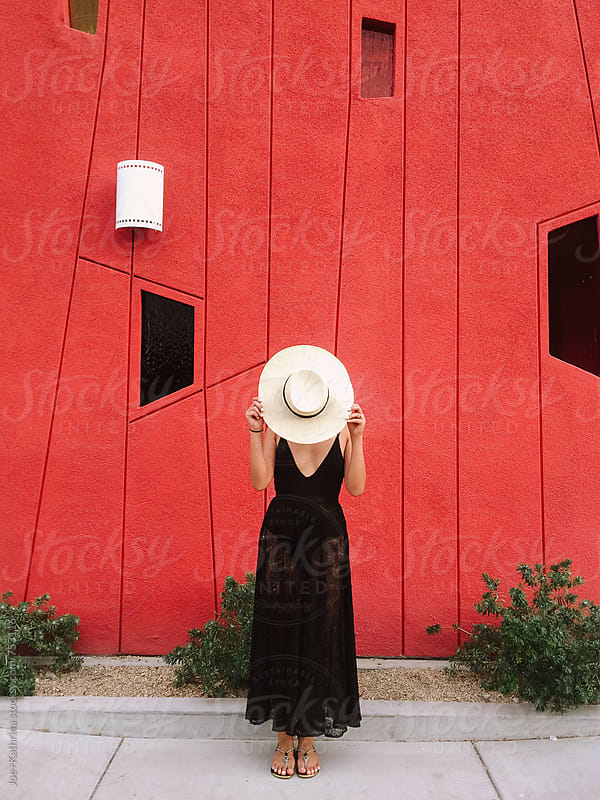 girl standing in front of red wall by Joe+Kathrina for Stocksy United
