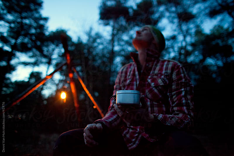Man sitting in the woods next to a lantern by Denni Van Huis for Stocksy United