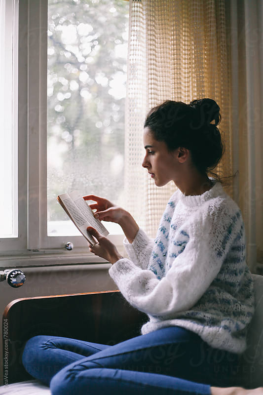Beautiful woman reading a book in her room near the window  by VeaVea for Stocksy United