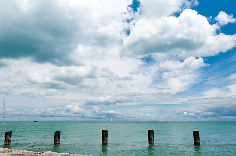 big blue skies filled with puffy clouds over Lake Michigan by Margaret Vincent for Stocksy United