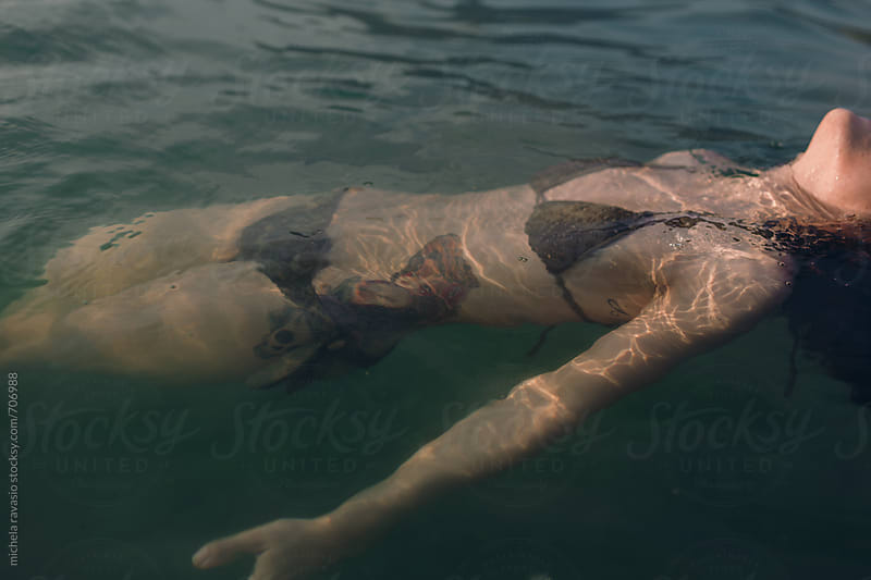 Woman with tattoo relaxing in the water by michela ravasio for Stocksy United