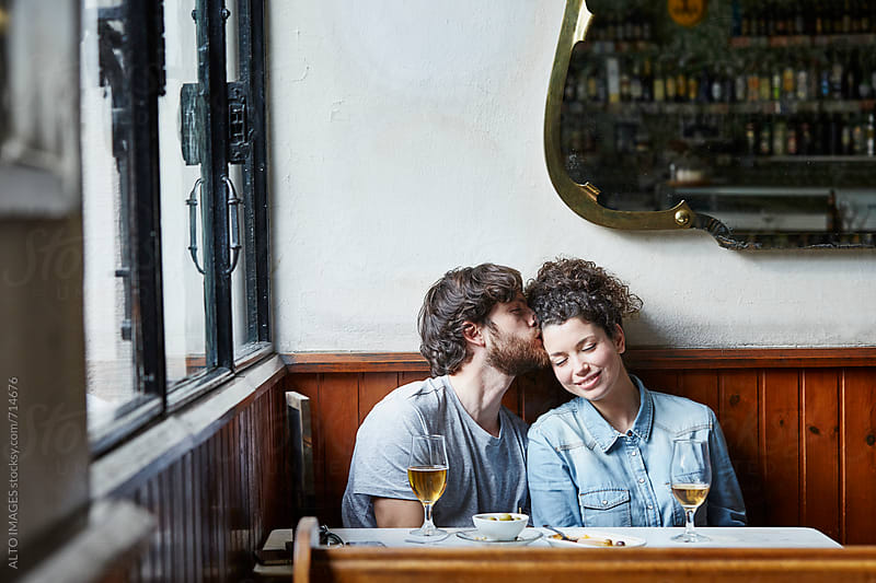 Man Kissing Woman In Restaurant by ALTO IMAGES for Stocksy United