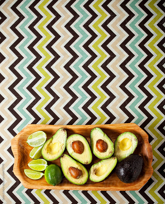 Food: Avocados and Limes on a Wooden Tray by Sean Locke for Stocksy United
