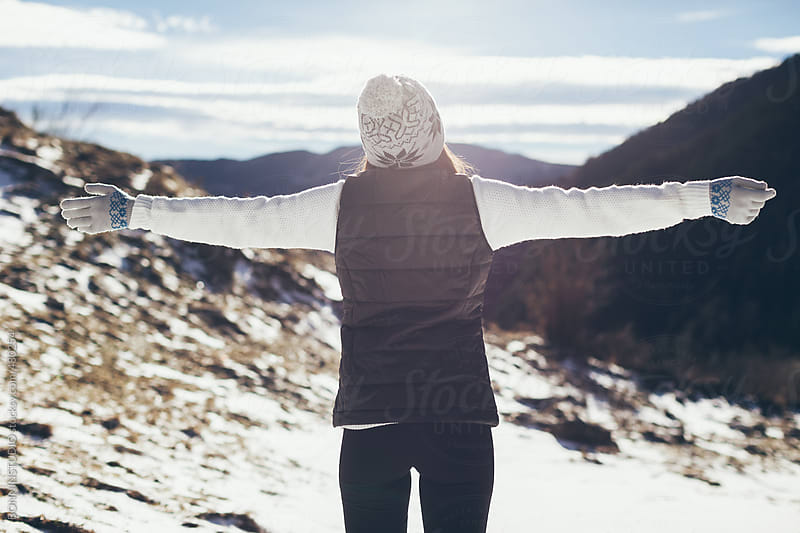 Back view of young woman looking a beautiful snowy landscape in winter.  by BONNINSTUDIO for Stocksy United