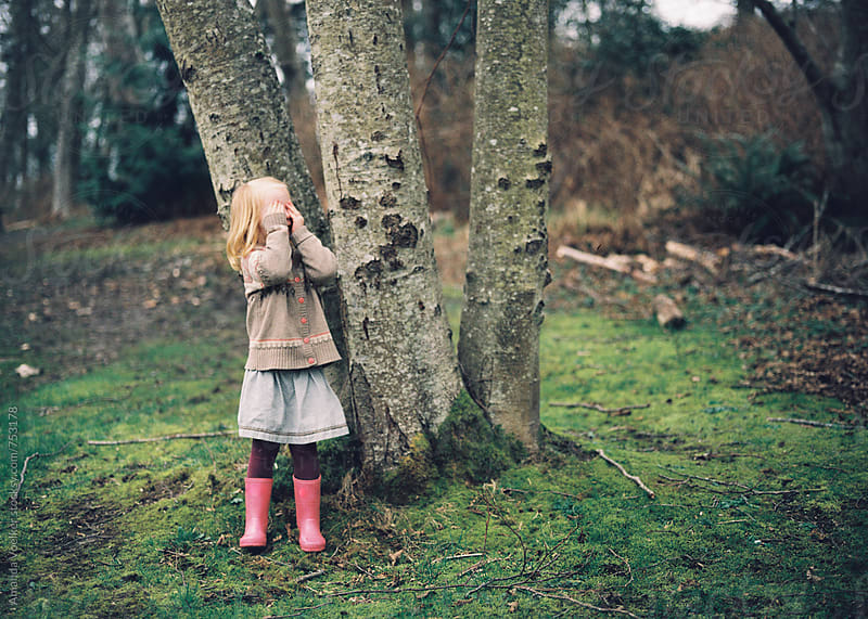 Young Girl plays hide and seek in the woods in early spring by Amanda Voelker for Stocksy United