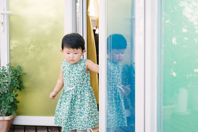 Toddler girl standing at a glass door by Maa Hoo for Stocksy United