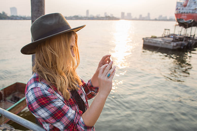 Blonde woman taking a photo of a sunset  by Jovo Jovanovic for Stocksy United