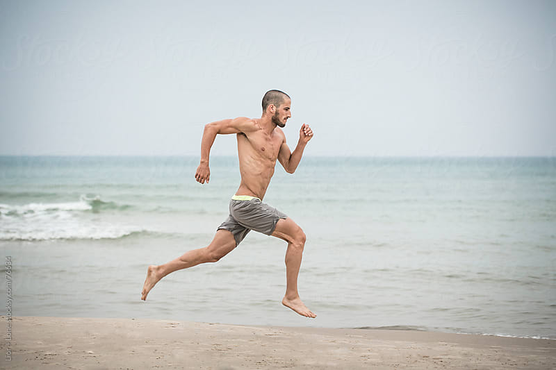 Young handsome athlete running in the beach by Lior + Lone for Stocksy United