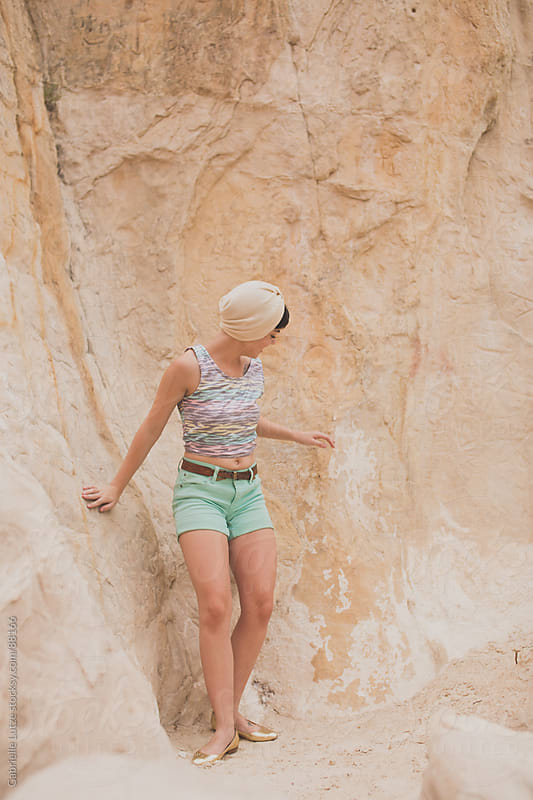 Summery girl climbing on white rock by Gabrielle Lutze for Stocksy United