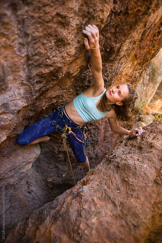 Young woman rock climbing a narrow crack outdoor by RG&B Images for Stocksy United