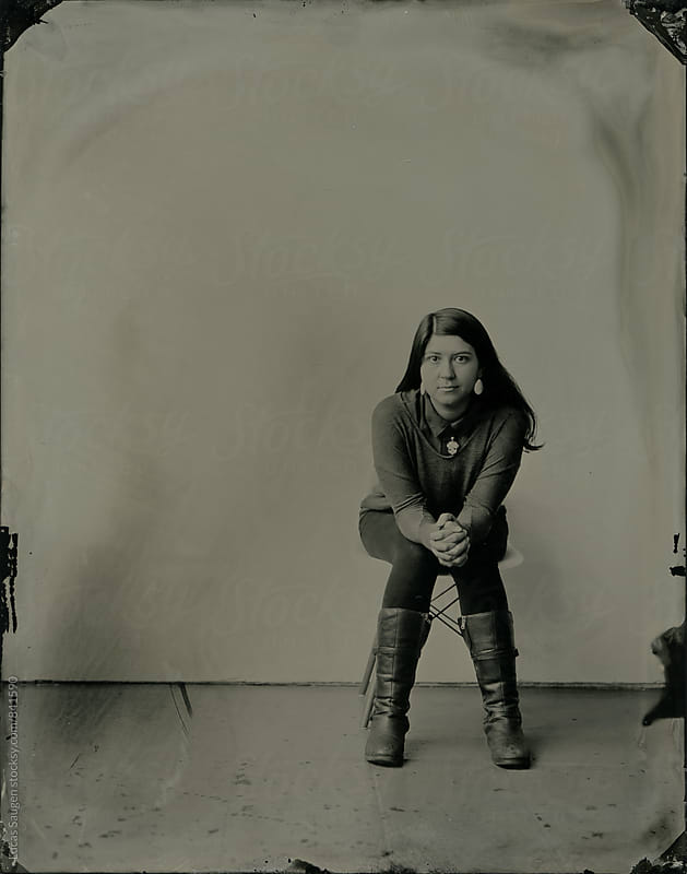 Wet plate tintype of a girl sitting on a chair. by Lucas Saugen for Stocksy United
