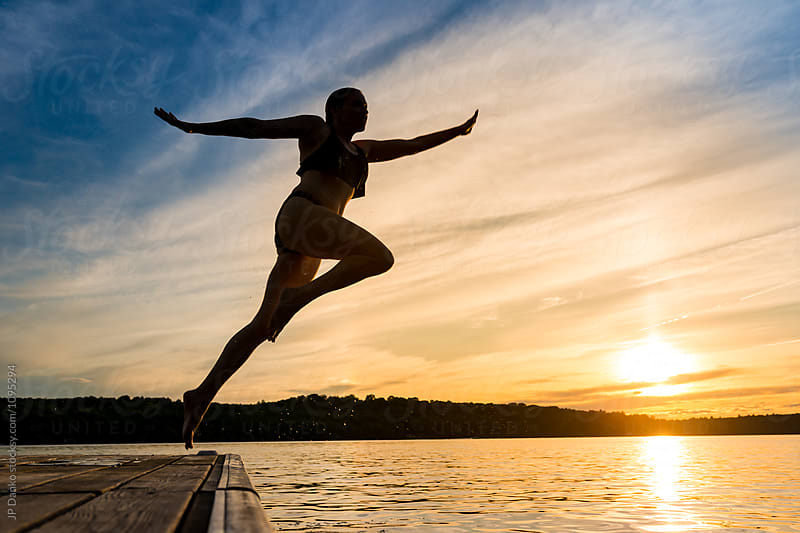 Woman Jumping Off Of Dock Into Warm Summer Cottage Lake At Sunset by JP Danko for Stocksy United