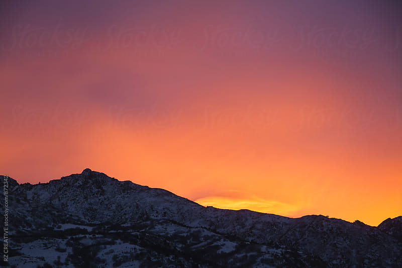 Colorful sunset over snow covered mountains in the high desert. by Robert Zaleski for Stocksy United