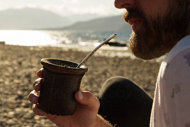 Bearded man drinking mate near a lake. by Leandro Crespi for Stocksy United