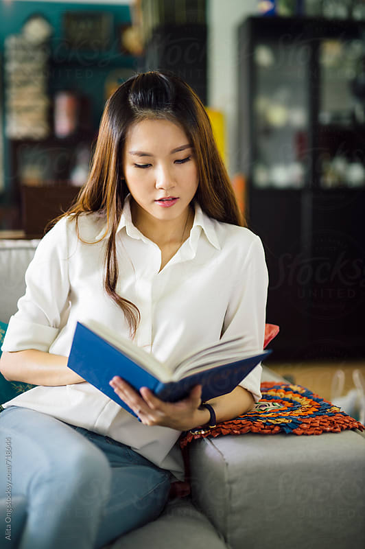 A young lady sitting on sofa while reading a book by Alita Ong for Stocksy United