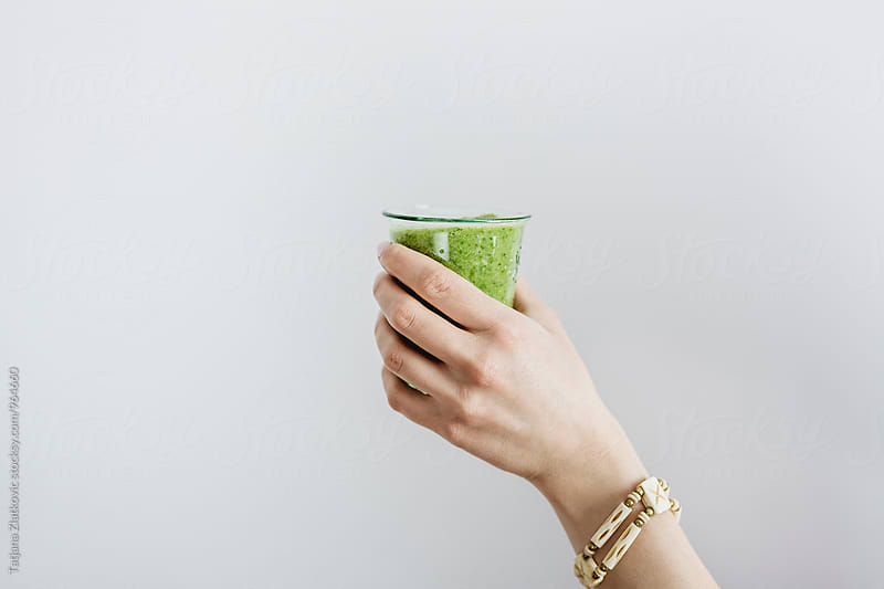 Hand holding green smoothie by Tatjana Zlatkovic for Stocksy United