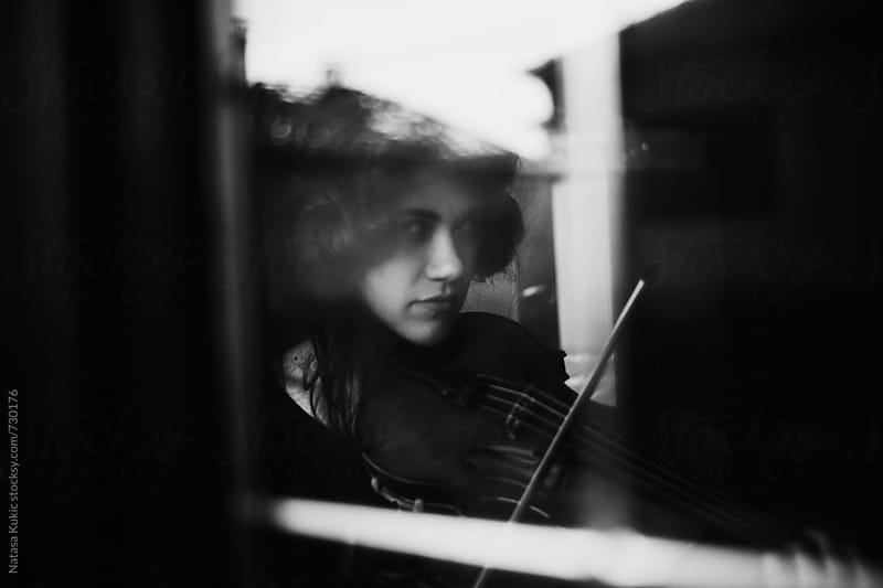 Girl playing violin shot through the glass,slightly out of focus by Natasa Kukic for Stocksy United