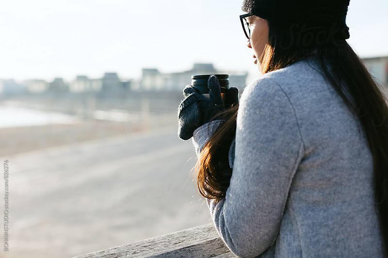 Woman holding a coffee thermos by the beach on winter. by BONNINSTUDIO for Stocksy United