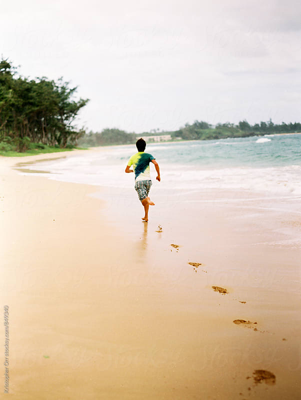 Running on beach in Hawaii by Kristopher Orr for Stocksy United