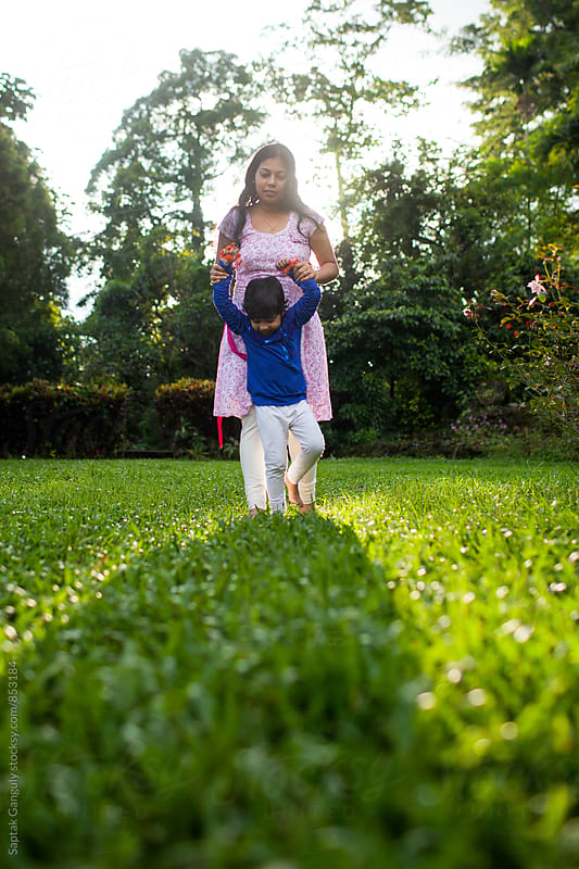 Mother helping her daughter walk on the grass by Saptak Ganguly for Stocksy United