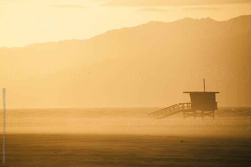 California beach sunset with lifeguard cabin in Venice beach, Los Angeles by Alejandro Moreno de Carlos for Stocksy United