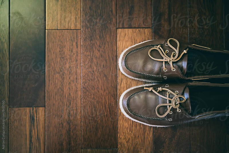 Brown leather shoes on a wooden floor by Adrian Cotiga for Stocksy United