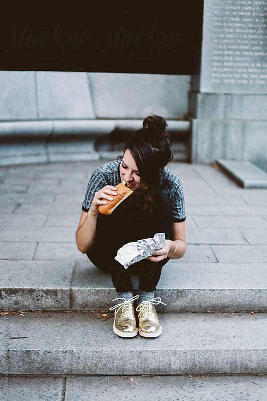 Woman sitting on stairs eating a hot dog by Treasures & Travels for Stocksy United